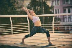 La mujer joven hermosa practica el asana Virabhadrasana 1 de la yoga - la actitud 1 del guerrero en la terraza en la puesta del s Fotos de archivo