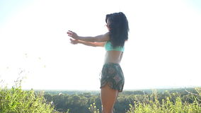 La mujer joven hermosa practica movimientos y posiciones de la yoga al aire libre respecto a un clifftop increíble almacen de metraje de vídeo
