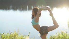 La mujer joven hermosa practica movimientos y posiciones de la yoga al aire libre respecto a un clifftop increíble metrajes