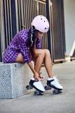 La mujer joven hermosa puso pcteres de ruedas y los cordones el atar Fotografía de archivo