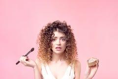 La mujer joven hermosa que aplica el polvo de la fundaci?n o se ruboriza con el cepillo del maquillaje fotos de archivo libres de regalías