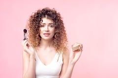 La mujer joven hermosa que aplica el polvo de la fundaci?n o se ruboriza con el cepillo del maquillaje imagenes de archivo