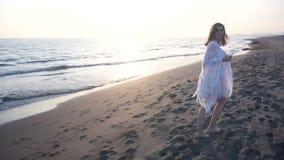 La mujer joven hermosa que camina en la playa hacia, da vuelta alrededor y llama para ir con ella almacen de metraje de vídeo