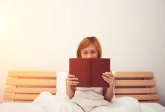 La mujer joven hermosa que dormía en la cama después de leyó un libro con Fotos de archivo libres de regalías