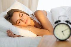 La mujer joven hermosa que duerme mientras que miente en cama comfortablemente y rayo de sol amanece dichosamente en su cara Fotografía de archivo libre de regalías