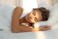 La mujer joven hermosa que duerme mientras que miente en cama comfortablemente y rayo de sol amanece dichosamente en su cara Foto de archivo libre de regalías