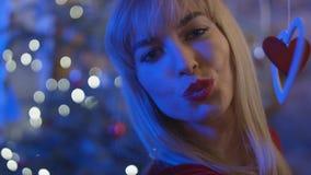 La mujer joven hermosa que envía un beso sobre bokeh de la Navidad se enciende Foto de archivo libre de regalías