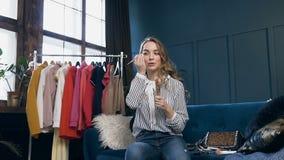 La mujer joven hermosa que habla compone el cepillo durante el vídeo que tira para el blog de la belleza almacen de video