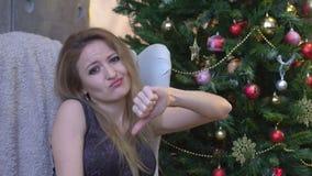 La mujer joven hermosa que muestra los pulgares abajo firma para tener aversión, en fondo del árbol de navidad metrajes