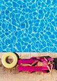 La mujer joven hermosa que ponía encendido sunbed en el poolside imagen de archivo libre de regalías