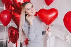 La mujer joven hermosa que presenta con el corazón rojo hincha en un cuarto blanco Fotografía de archivo libre de regalías