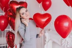 La mujer joven hermosa que presenta con el corazón rojo hincha en un cuarto blanco Fotos de archivo libres de regalías
