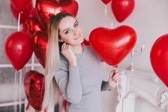 La mujer joven hermosa que presenta con el corazón rojo hincha en un cuarto blanco Imagenes de archivo
