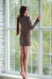 La mujer joven hermosa que se coloca solamente cerca de ventana con lluvia cae Muchacha atractiva y triste Concepto de soledad Fotos de archivo