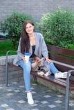 La mujer joven hermosa que se sienta en banco de madera y goza con su perro esquimal lindo del pequeño perro Fotografía de archivo libre de regalías