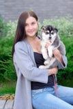 La mujer joven hermosa que se sienta en banco de madera y goza con su perro esquimal lindo del pequeño perro Fotos de archivo libres de regalías