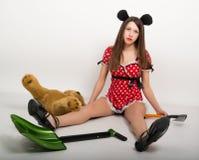 La mujer joven hermosa que se sienta en el piso en un vestido corto con los lunares, al lado de él es una pala y un oso de peluch Fotos de archivo libres de regalías