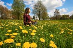 La mujer joven hermosa reflexiona sobre un prado con muchos dientes de león en el sol de la primavera imagenes de archivo