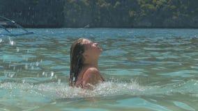 La mujer joven hermosa salpica el agua vidriosa del océano moviendo de un tirón su pelo detrás Muchacha en juegos de las vacacion almacen de video