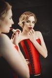 La mujer joven hermosa se coloca delante de un espejo y pinta sus labios Ilustración retra de la vendimia style Imagen de archivo libre de regalías
