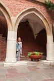 La mujer joven hermosa se coloca que se inclina en una columna en un paso arqueado Imagen de archivo libre de regalías