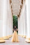 La mujer joven hermosa se está colocando entre las columnas Imágenes de archivo libres de regalías