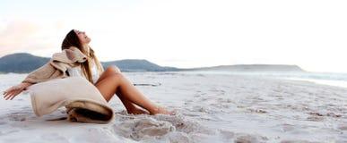 La mujer joven hermosa se relaja en la playa fotos de archivo
