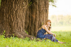 La mujer joven hermosa se sentó en raíces del árbol grande viejo y miraba para arriba soñador Imagen de archivo libre de regalías