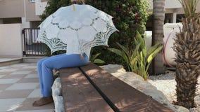 La mujer joven hermosa se sienta en banco y abre el paraguas decorativo almacen de video