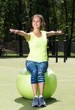 La mujer joven hermosa se sienta en la bola del ajuste Ejercicio en el aire abierto Fotos de archivo libres de regalías