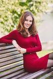 La mujer joven hermosa se sienta en un banco Retrato al aire libre foto de archivo libre de regalías
