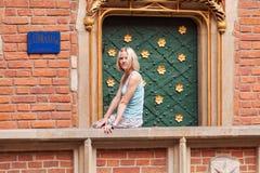 La mujer joven hermosa se sienta en un parapeto contra un fondo de la pared de ladrillo Imagenes de archivo