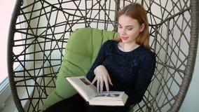 La mujer joven hermosa se sienta en una silla pendiente con la taza de té o de café caliente almacen de metraje de vídeo