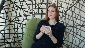 La mujer joven hermosa se sienta en una silla pendiente con la taza de té o de café caliente metrajes