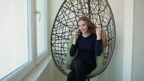 La mujer joven hermosa se sienta en una silla y hablar en el teléfono metrajes