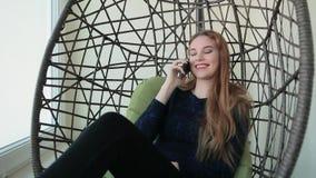 La mujer joven hermosa se sienta en una silla y hablar en el teléfono almacen de metraje de vídeo