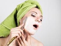 La mujer joven hermosa se vistió en afeitados de una toalla de baño con una maquinilla de afeitar recta industria de la belleza y Fotos de archivo libres de regalías