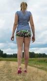 La mujer joven hermosa se vistió en pantalones cortos y soportes de una camiseta en el camino contra el cielo y la hierba Foto de archivo