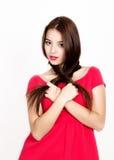La mujer joven hermosa se vistió en un vestido rojo, sostiene las coletas Tiro del estudio Foto de archivo libre de regalías