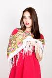 La mujer joven hermosa se vistió en un vestido rojo y coloreó la bufanda que presentaba en estudio Imágenes de archivo libres de regalías