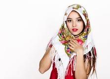 La mujer joven hermosa se vistió en un vestido rojo y coloreó la bufanda que presentaba en estudio Imagen de archivo libre de regalías