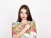La mujer joven hermosa se vistió en un vestido rojo y coloreó la bufanda que presentaba en estudio Imagenes de archivo