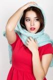 La mujer joven hermosa se vistió en un vestido y una bufanda rojos que presentaban en estudio Foto de archivo libre de regalías