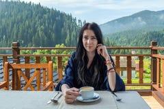 La mujer joven, hermosa, soñolienta bebe el café en un fondo de montañas en la madrugada fotos de archivo