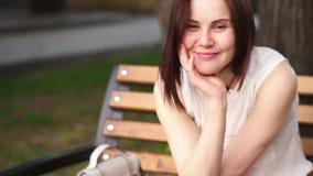 La mujer joven hermosa sonríe misterioso, sentándose en un banco en un parque del verano Retrato de una mujer al aire libre almacen de video