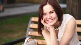 La mujer joven hermosa sonríe misterioso, sentándose en un banco en un parque del verano Retrato de una mujer al aire libre almacen de metraje de vídeo