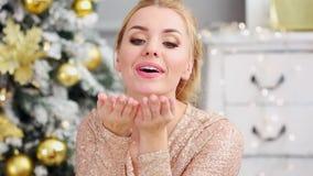 La mujer joven hermosa sopla un confeti de las manos cerca del árbol de navidad metrajes