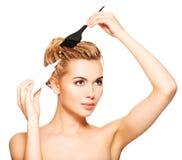 La mujer joven hermosa teñe su pelo Fotografía de archivo libre de regalías