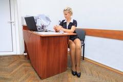 La mujer joven hermosa trabaja en oficina foto de archivo