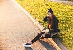 La mujer joven hermosa y de la moda se sienta con un monopatín en el tablero Fotografía de archivo